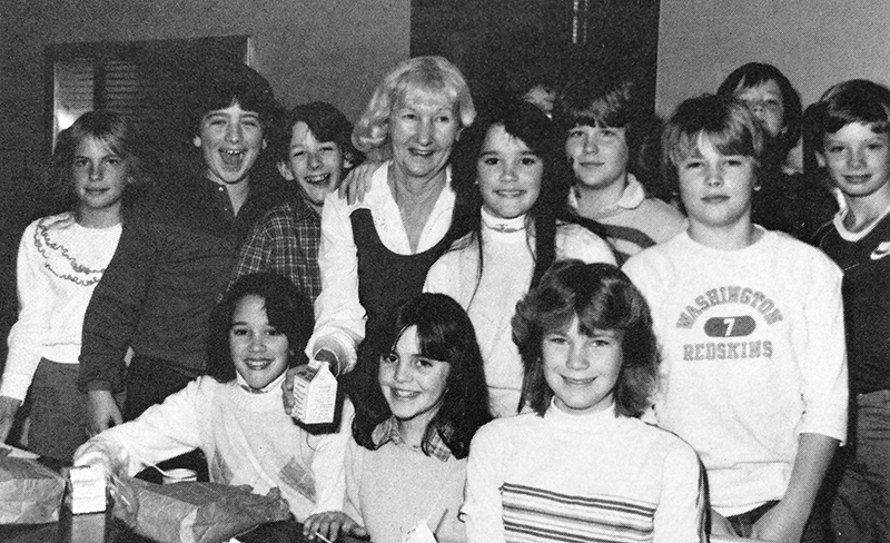 Black and white photograph of Eleanor Williams from our 1983 to 1984 yearbook. She is standing in the cafeteria surrounded by a large group of smiling students.