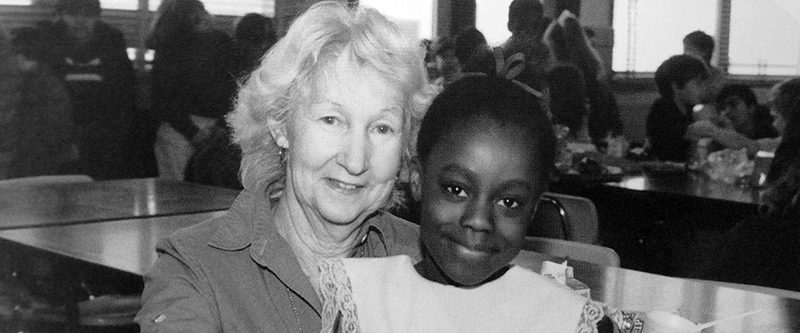 Black and white photograph of Eleanor Williams from our 1989 to 1990 yearbook. She is seated in the cafeteria and is posing with a female student.
