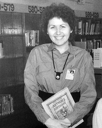 Black and white photograph of Kathryn Nutter from our 1989 to 1990 yearbook. She is pictured standing in the library holding a book in her hands. The book is from the Arthur series and is entitled Arthur's Birthday.