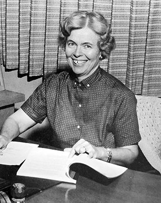 Black and white photograph of Principal Evelyn Lynn from our 1965 to 1966 yearbook. She is seated at her desk, papers in hand, and is smiling broadly at the camera.